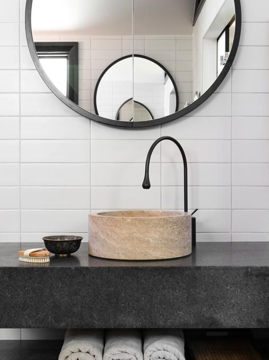 Nice wooden bathroom sink and stacked subway tile with black faucet.