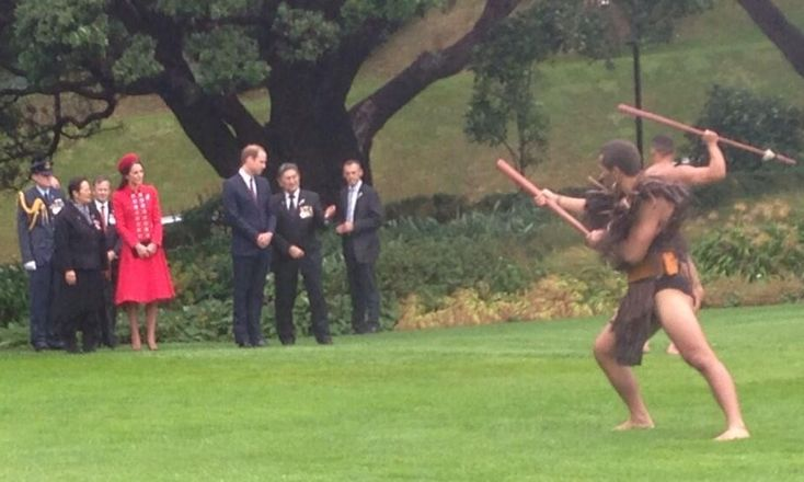 """Prince William and Catherine, Duchess of Cambridge, aka Kate Middleton, receive a traditional Maori welcome at Government House, in Wellington, NZ. She is wearing the Russian Greatcoat by Catherine Walker, the """"Seaford"""" style hat by Gina Foster, brown suede Emmy clutch and heels, and a diamond and platinum brooch in the shape of a fern (a national symbol of New Zealand), on loan from HM the Queen. 4/07/14"""