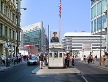 Checkpoint Charlie as tourist attraction. The ersatz guard house viewed from what was the American sector. Beyond it is a mast with an image of a Soviet soldier.(June 2003)