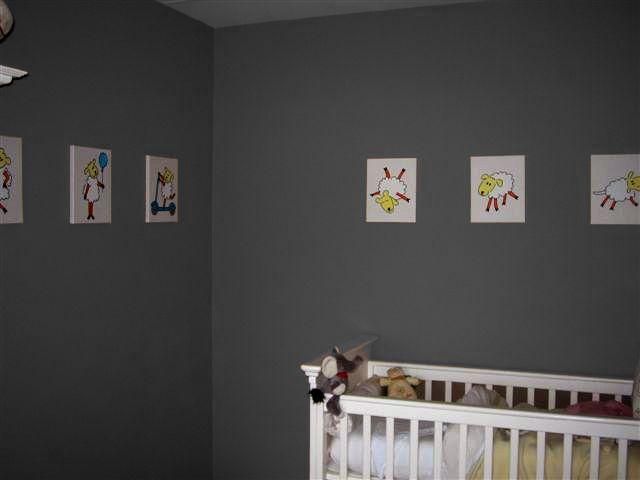 Babykamer in grijs. Een vrij donkere tint grijs kan ook heel mooi werken in de babykamer. De schilderijen zijn rustig gehouden in een zachte creme-tint. 6 Schilderijen met schaapjes.
