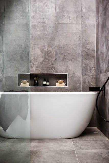 semi donkere tegel op wand en vloer. het witte bad steekt erbij af.