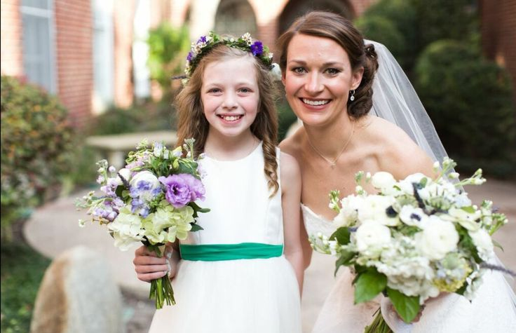 the flower girl carries a posy of green hydrangea, lavender scabiosa, white ranunculus, lavender stock,  purple lisianthus, lavender, white anemones & lemon leaf  wrapped in cream satin ribbon. she also wore a flower  crown of greenery with lavender scabiosa, white wax flower & white ranunculus for flower girl