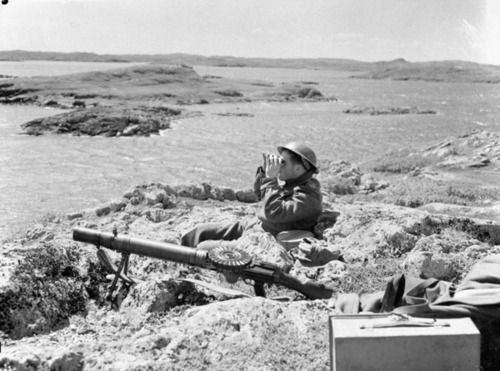 Soldier of the 1st Battalion, The Black Watch (Royal Highland Regiment) of Canada, keeping watch with a Lewis automatic machine gun at his side in Botwood, Newfoundland on 22 June, 1940.
