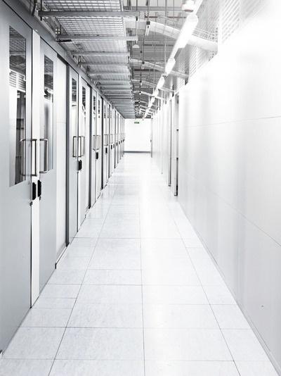 Ein langer Flur mit vielen Türen, hinter den sich wahrscheinlich ebenfalls Zellen befinden.