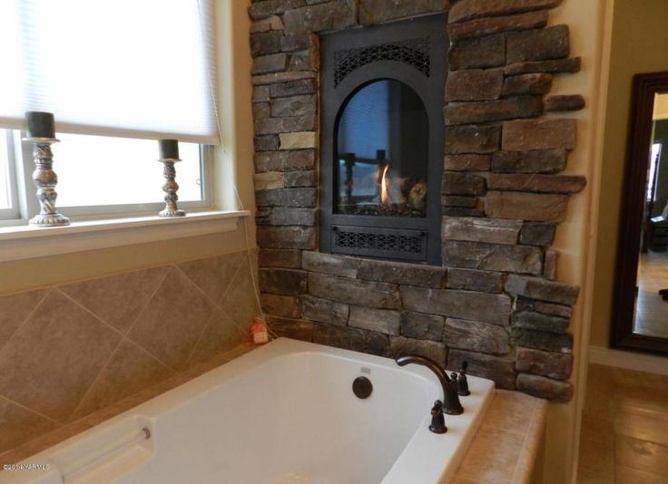 Faux rock wall and fireplace insert above bathtub