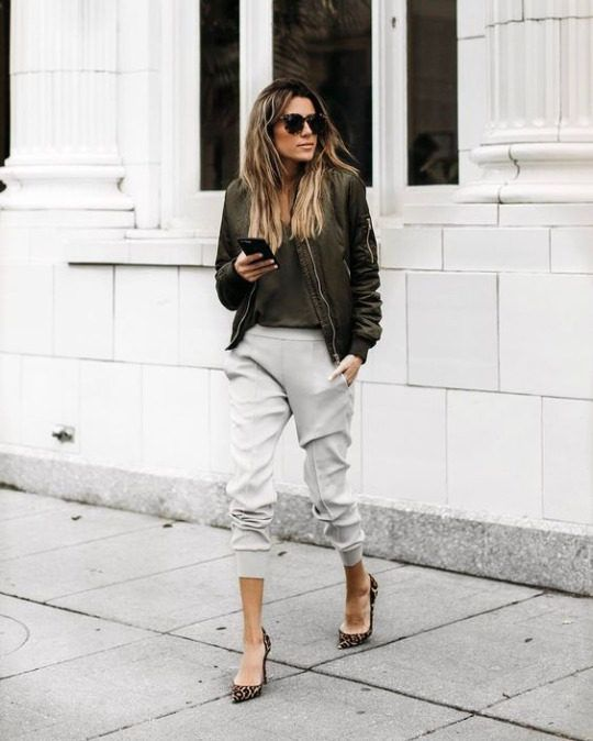 Christine Andrew is seen here in leopard print heels, cropped jogger-style pants, and a matching khaki top and bomber jacket. She wears sleek black shades to complete this spring outfit. Jacket: ILY Couture.