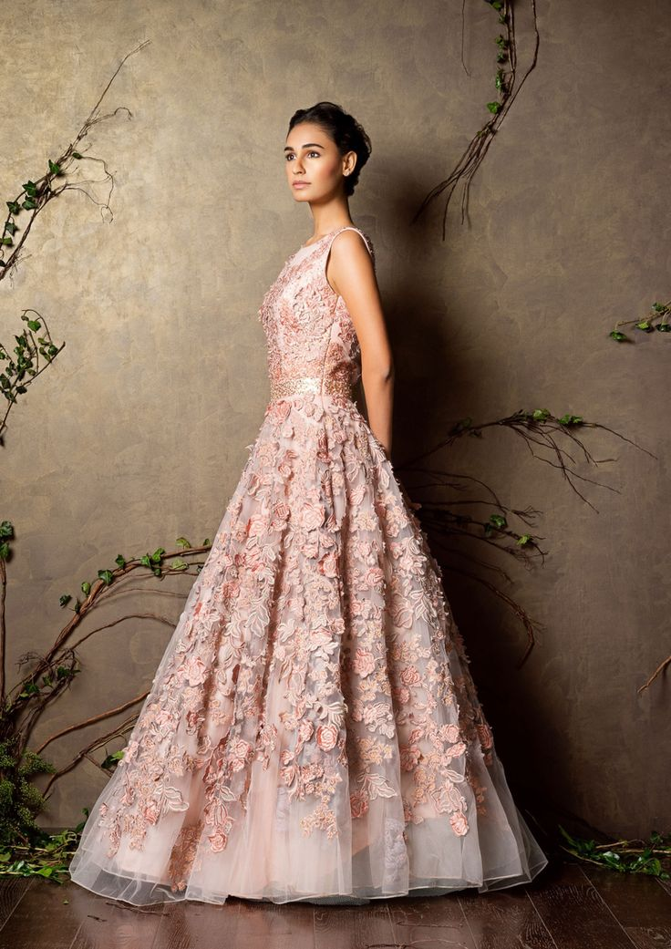 A peach pearl tulle gown with exquisite khat work embroidery all over. A melange of texture and hints of gold add a fairytale feel to the outfit.