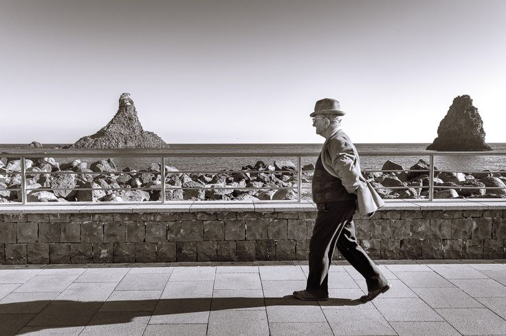 Il siciliano - One old man walking alone in the seafront of Acitrezza, Catania, Italy