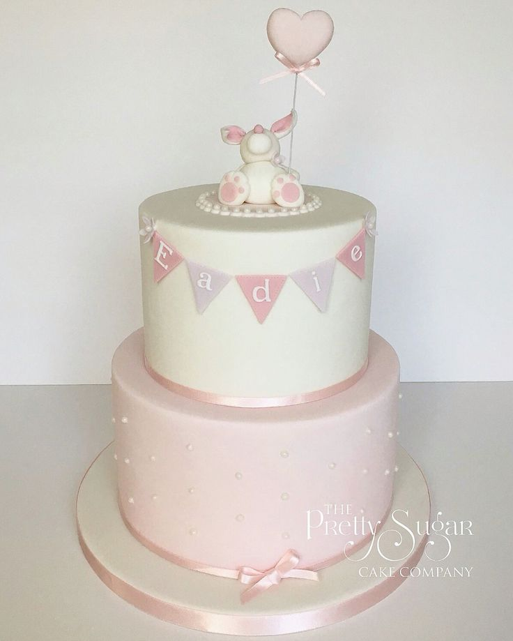 Pink and white christening cake with bunting and pearl details and bunny with balloon topper