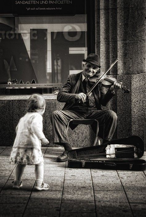 ZsaZsa Bellagio. Street musician performs while a child dances. Black and white photograph. #photography