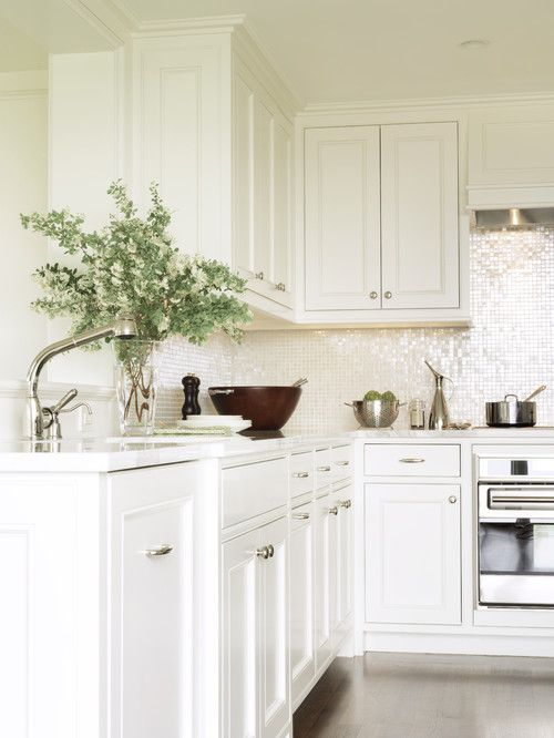 White cabinets look best when they play off opposing elements. The simple white cabinets look more interesting when juxtaposed with a sparkling glass backsplash.