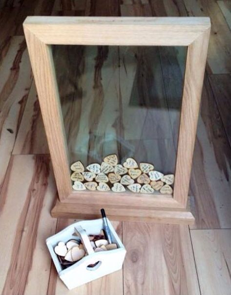 Great idea instead of a guest book. Buy 2 frames, remove the backs from both, keep glass and stick together. Litter hearts of wood for messages. Beautiful!
