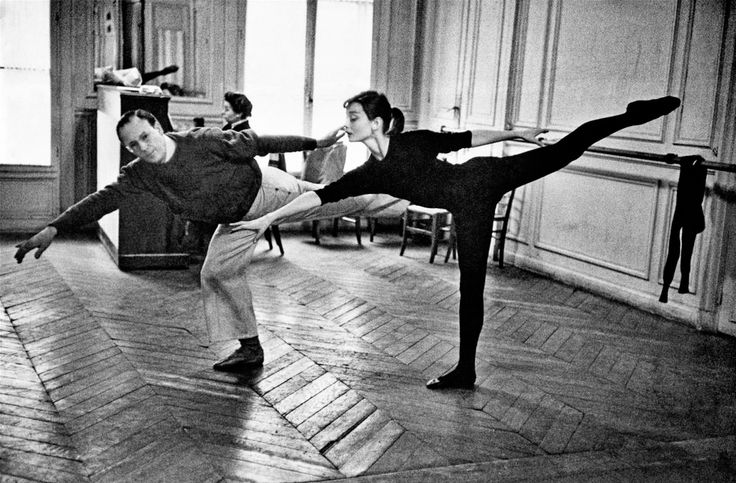 Audrey Hepburn with ballet coach Lucien Legrand, the first dancer and choreographer for the Paris Opera Ballet, at a dance rehearsal for her film Funny Face, Paris, France, 1956.