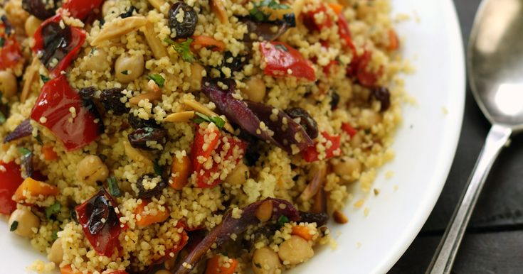 An exotic and colorful Moroccan couscous dish with chickpeas, roasted red peppers and carrot, toasted almonds, and plump raisins.