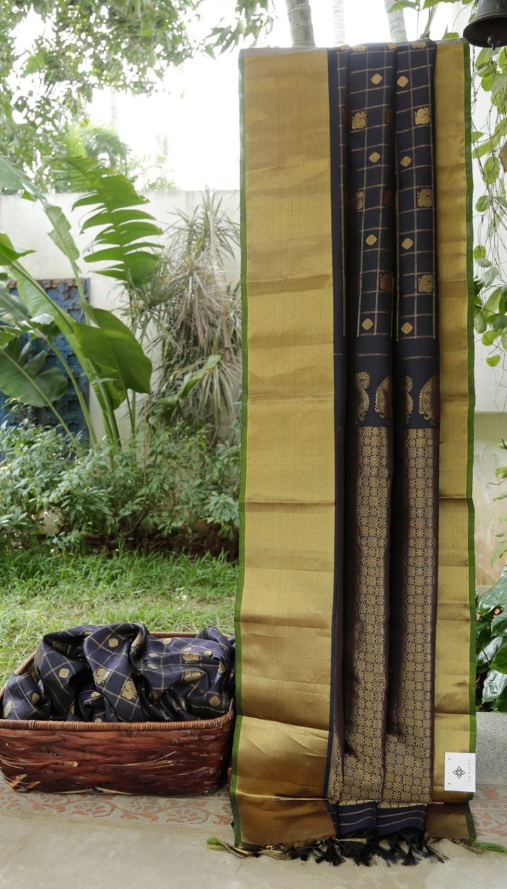 This gadwal silk is in black that is chequered with gold zari with bhuttas in squares. The border is enmeshed with gold zari with a moss green selvedge and the pallu is intricately woven with gold …