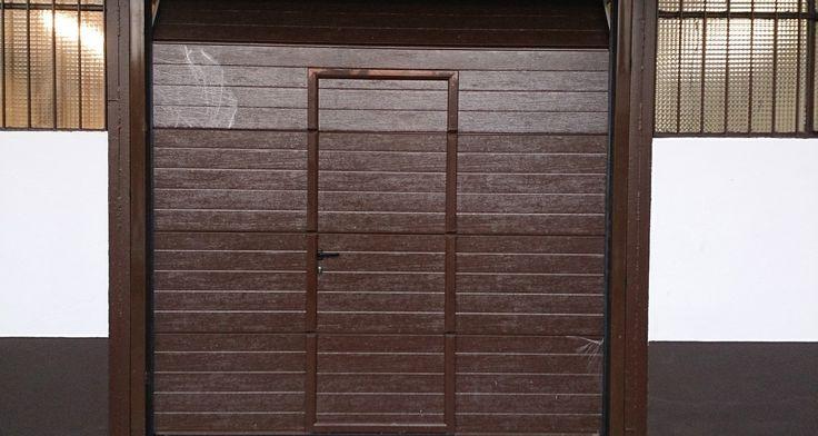 Puerta seccional instalada por la empresa de instalación de puertas de garaje servidoors, líder en instalación de puertas seccionales, está puerta es de color marrón imitación a madera, con una puerta peatonal, ademas va con un motor en el techo que hace que esta puerta sea una puerta seccional automática con motor en el techo.