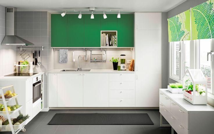 Witte keuken met groene accentdeuren en witte werkbladen, in combinatie met roestvrijstalen afzuigkap en witte oven