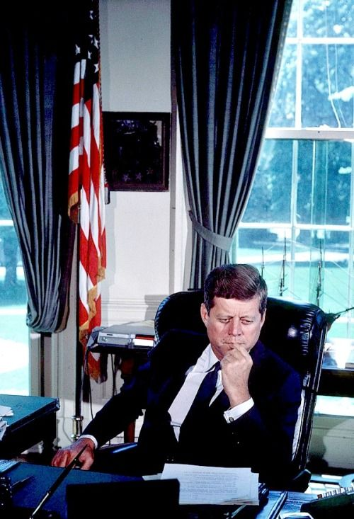President Kennedy at his desk in the Oval Office, c 1961.