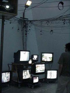Game Station, 2002, vidéo installation, Documenta 11, Kassel, 2002. Environnement constitué d'un long couloir éclairé par des lumières colorées aux couleurs du Cameroun conduisant à un espace de rue sombre avec un hangar à bois, une lampe de rue et des postes de téléviseurs et des radios diffusant images et sons du Cameroun et du monde entier.