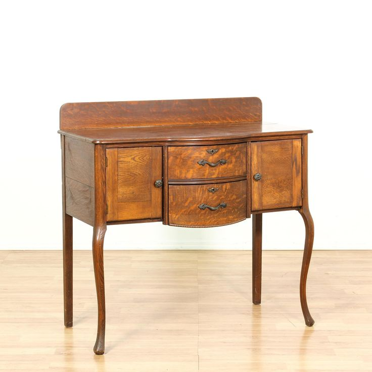 This antique sideboard buffet is featured in a solid wood with a gorgeous tiger oak finish. This vintage server bar has delicate curved cabriole legs, 2 curved front doors and 2 cabinets. Great for serving drinks in a small space! #americantraditional #storage #buffet #sandiegovintage #vintagefurniture