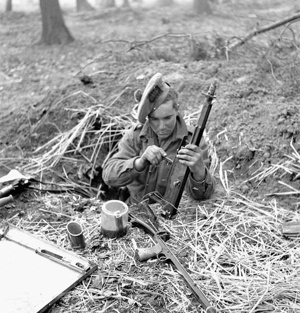 Private J.E. LeBlanc, Queen's Own Cameron Highlanders of Canada, cleaning his Bren gun in a foxhole in the Hochwald, Germany, 5 March 1945.