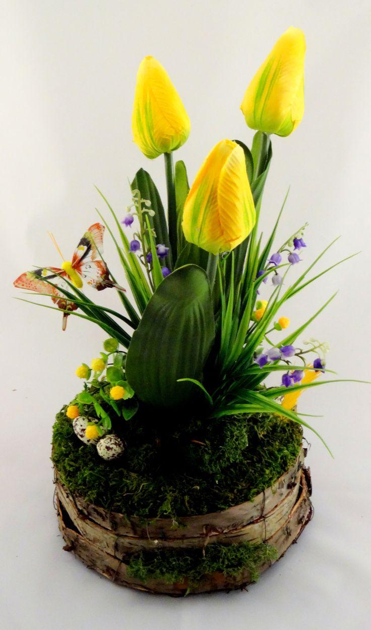 www.abgHomeArt.pl Ręcznie wykonany z dbałością o każdy szczegół wielkanocny stroik w podstawie wykonanej z kory brzozowej z kwitnącymi żółtymi tulipanami i niebieskimi konwaliami na trawce otulone mchem. Udekorowany nakrapianymi jajeczkami i motylkiem.     Efektowna i radosna wielkanocna dekoracja, która pięknie przyozdobi stół, komodę, czy też kominek, a także wprowadzi powiew wiosny. Idealny do każdego wnętrza.