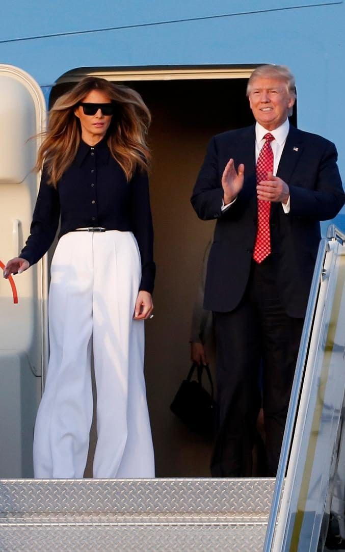 U.S. First Lady Melania Trump.. Michael Kors black button-front blouse, and Carolina Herrera belted white wide-legged pant..