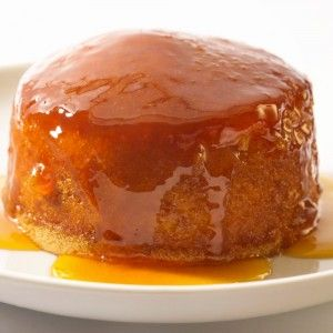 Treacle sponge drizzled with golden syrup and placed on a plate.