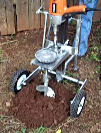 Post Drill by keithandbeatice -- Homemade post drill constructed from an auger, electric drill, sprockets, chain, bar stock, plate, and wheels. http://www.homemadetools.net/homemade-post-drill