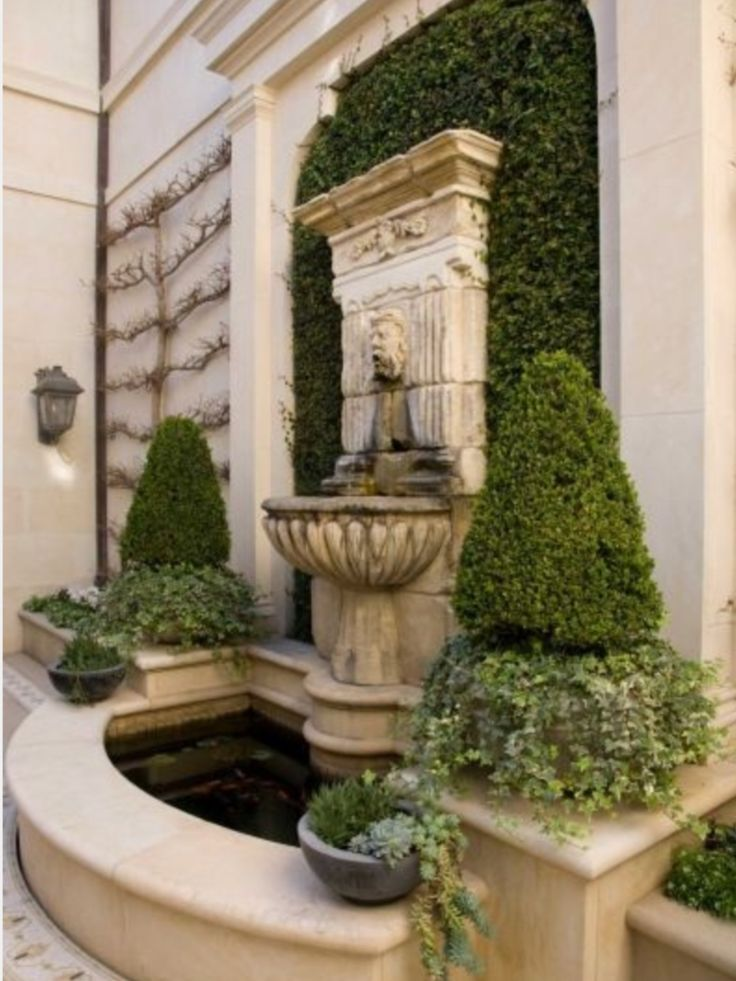 Wall fountain in courtyard; espalier and pair of topiary adjacent
