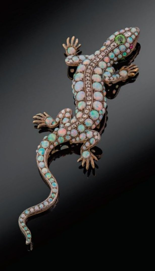 A late Victorian salamander brooch, pavé-set overall with graduated circular opal cabochons in silver and gold. Centred with a line of graduated cushion-shaped diamonds and the head set with a circular-cut demantoid garnet and with ruby eyes. Detachable brooch fitting. 10cm long. #Victorian #antique