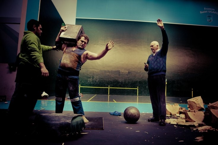 Lucia Herrero  A referee signals a completed move in a rectangular stone lifting competition. Having hoisted a 113kg stone to his shoulder with his right arm alone, the lifter raises his own left hand for flair.