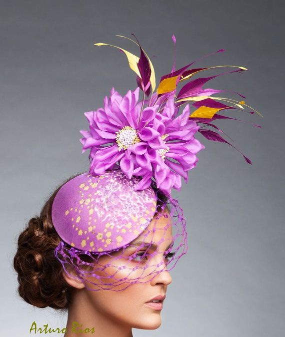From my new collection:  This Plum/Lavender/mauve mix fascinator is made on a round base covered with a plum/yellow printed silk fabric with a delicate beading design, embellished with a hexagonal netting, 5 Sunburst Blossoms and Plum and yellow rooster feathers. it includes a thin black elastic that you place around your head, its easy and softer to wear.  All my headpieces are hand made to order , please allow a week while we make it, if this is a rush order, please contact m...