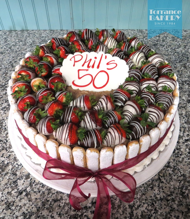 Strawberry Charlotte Torte —Yellow cake with strawberry mousse filling, buttercream icing, surrounded with lady fingers and topped with chocolate covered strawberries. A rich treat for strawberry lovers!