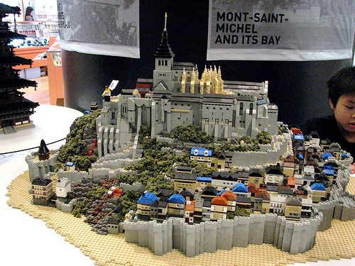 LEGO Mont-Saint-Michel. Mont Saint-Michel (pronounced: [mɔ̃ sɛ̃ mi.ʃɛl]; English: Saint Michael's Mount) is an island commune in Normandy, France. It is located approximately one kilometre (0.6 miles) off the country's northwestern coast, at the mouth of the Couesnon River near Avranches. 100 hectares (247 acres) in size, the island has a population of 44 (2009).[1]