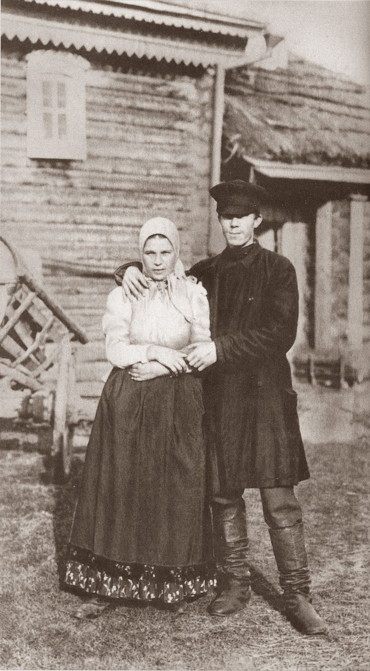 Russian peasant married couple wearing traditional casual dresses. Late 19th – early 20th century.