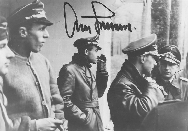 Lieutenant Colonel Adolf Galland with a cigar and a Lieutenant Colonel Werner Mölders among others, surrounded by other Luftwaffe officers standing on the porch of the Reich Chancellery.