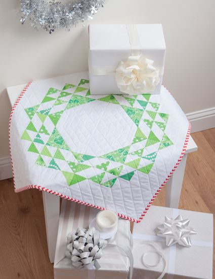 Stitch this pretty wreath table topper in a weekend! The center is left plain to showcase a centerpiece. By Cindy Lammon, author of Simply Modern Christmas.