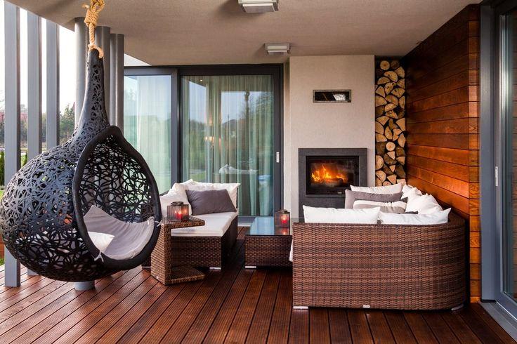 Na tarasie wygodne meble z polirattanu, efektowny hamak-gniazdo z lawy wulkanicznej, ciepłe drewno pod stopami.