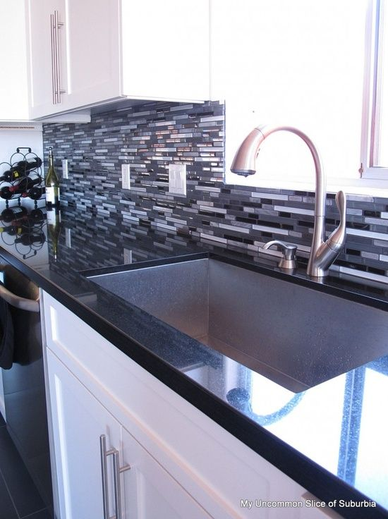 modern kitchen: white cabinets and black counter tops are perfectly tied together with that amazing 50 shades of grey backsplash and stainless steel hardware/appliances. the natural light is a winner as well :)