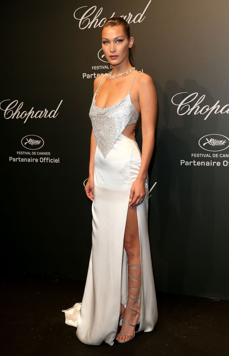 Bella Hadid look the ever stunning and sexy self, with wrap knee high sandals, a revealing white and crystal gown and a diamond necklace. She wore a slick back ponytail and dewy makeup. As seen at the Chopard Space Party. For glamour celebrity fashion Cannes Film Festival red carpet jewellery spotting travel here: http://www.thejewelleryeditor.com/jewellery/top-5/cannes-film-festival-red-carpet-jewellery-day-two/ #jewelry