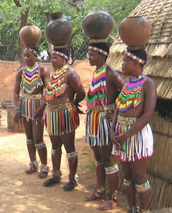 Africa   Zulu maidens wearing traditional beaded attire and carrying pots on their head.  South Africa    Photographer unknown