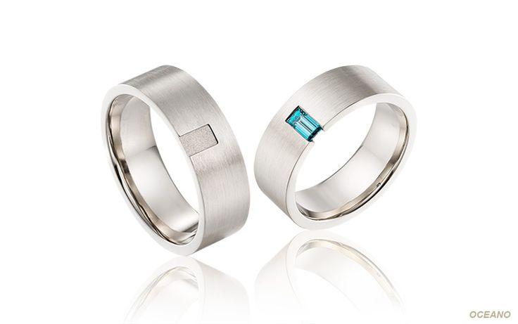 Trouwringen met blauwe diamant: de witgouden damesring is bezet met een fantastische baguette geslepen diamant. Bij de herenring is het diep gelegen gedeelte gezandstraald. Een set unieke ringen.