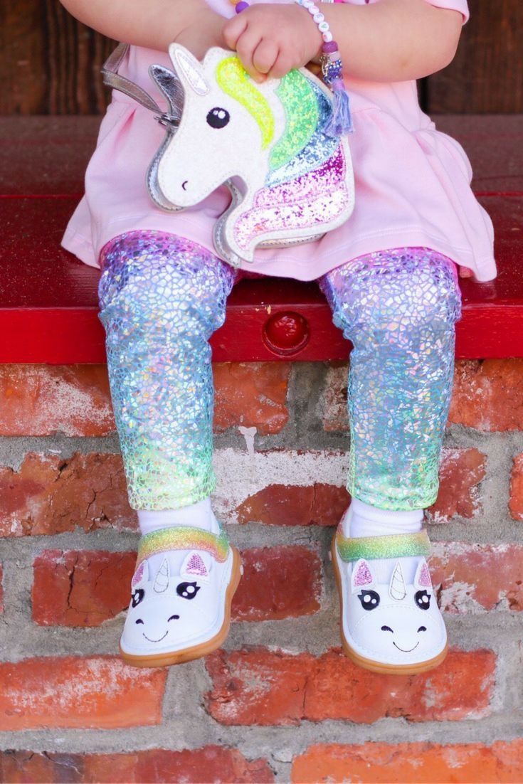 Fun Shoes for Kids from Wee Squeak: Unicorn | Kids and grown-ups alike are in LOVE with our whimsical Unicorn Shoes! Each Unicorn has a glittery rainbow tail strap, heart shaped cutie mark, and a magical horn. No two rainbow straps are alike!