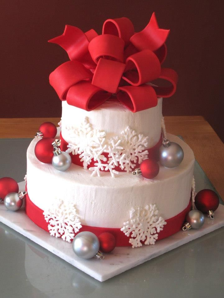 """Christmas Wedding Cake - My very first wedding cake, for a Christmas themed wedding on 12/12/12.  Bottom tier = 10"""" round, top tier = 6"""" round.  Both tiers were WASC with cookies & cream filling, covered in vanilla almond BC.  Handmade RI snowflakes, fondant ribbons & bow; artificial Christmas ornaments."""