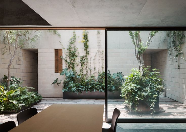 Architecture studio Ambrosi Etchegaray has slotted four new homes behind a historic facade in Mexico City, but left enough space for three secluded patios