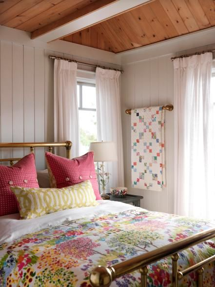 The sun was the inspiration for the bright colors in this guest bedroom. The recycled white-painted pine paneling on the walls gives a neutral backdrop to the colorful fabric schemes. The division in the windows brings charm into the space, while the brass bed adds a robust element to the summer cottage bedroom.