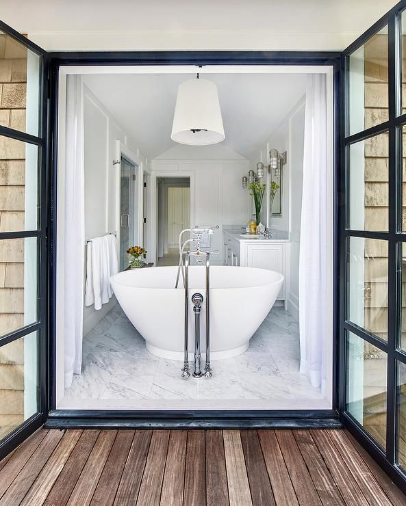 White cottage bathroom features a white tapered drum pendant light which hangs over a freestanding bathtub placed in front of steel doors dressed in white curtains which open to the deck.