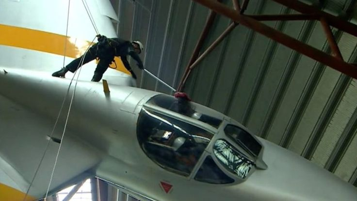 Specialist cleaners dangle on ropes attached to the ceiling so they can dust aircraft on display.