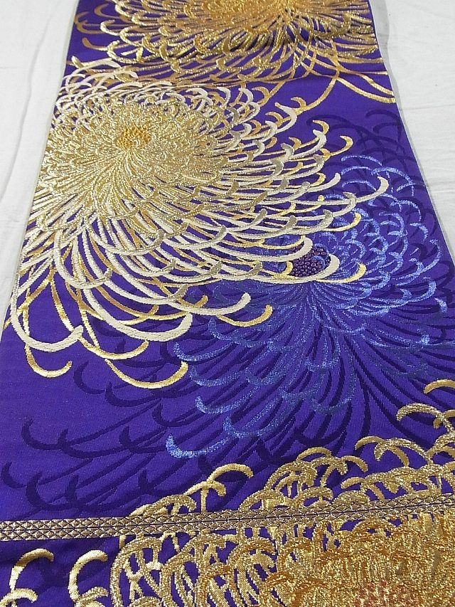 This is an elegant fukuro obi with dazzling 'kiku' (chrysanthemum) pattern, which is woven dynamically with gold threads in the color of vibrant dark purple background. Textile is exquisite silk, and has soft touch.